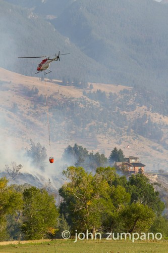 After loading water from the Yellowstone River a helicopter returns to the Pine Cr Fire